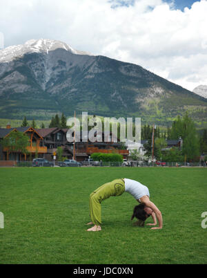 Young woman practicing yoga, doing bridge exercise outdoors in Centennial Park in Canmore, town in Alberta's Rockies - Stock Photo