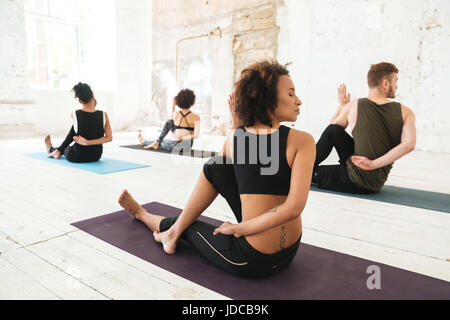 Group of multicultural young people practicing yoga in a studio - Stock Photo