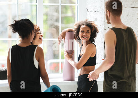 Smiling african woman talking with friends while doing yoga in gym - Stock Photo