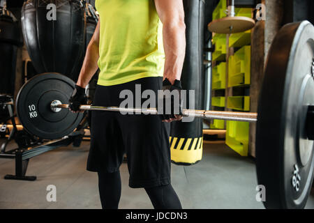 Cropped image of a young muscular man with barbell at the gym - Stock Photo