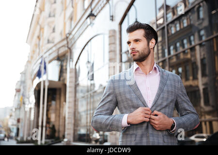 Portrait of a young handsome man buttoning his jacket in a city area - Stock Photo