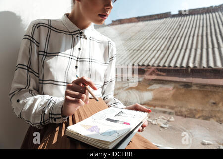Cropped image of a young woman artist drawing sketches while sitting on a windowsill at studio - Stock Photo