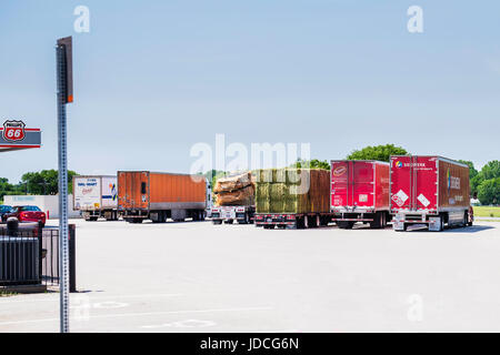 A line of semi trucks parked at Belle Plains, a truck stop with a Phillips 66 station on I-35 in Kansas, USA. - Stock Photo