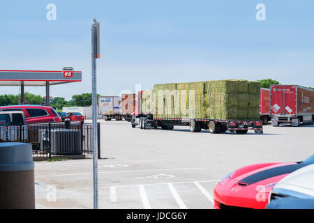 A semi truck with a load of hay pulls into Belle Plains, a rest stop on I-35 in Kansas, USA. - Stock Photo