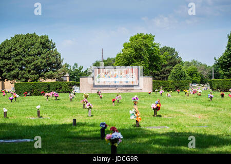 An area of a cemetery Called Last Supper, showing an image of the Last Supper on the lawn with decorated Memorial - Stock Photo