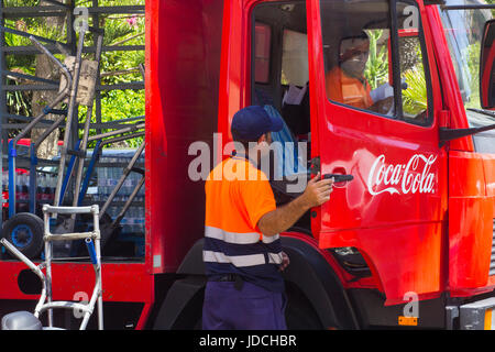 A pair of male employees make a delivery of Coca Cola to a local supermarket in Playa Las Americas in the canary - Stock Photo