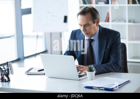 mature serious businessman working and typing on laptop on workplace in office - Stock Photo