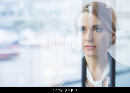 Portrait of pensive blonde businesswoman in formal wear looking through glass - Stock Photo
