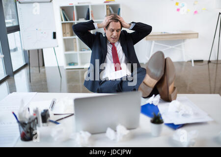 Stressed mature businessman sitting at table with laptop and gesturing - Stock Photo
