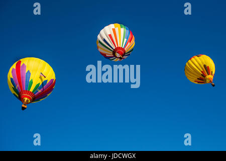 Three Hot-Air Balloons flying in a Blue Sky - Stock Photo
