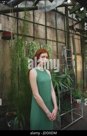 Portrait a young redheaded woman in dress standing with potted plants on a background - Stock Photo