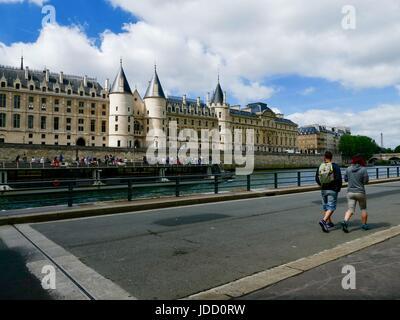 Two men walking along Parc Rives de Seine, looking at a passing tourist boat. Paris, France - Stock Photo