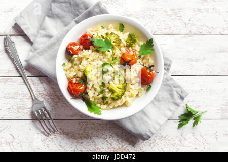 Bulgur with Vegetables: tomatoes, broccoli and parsley on white wooden background - healthy homemade organic vegan - Stock Photo