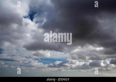Grey storm clouds gathering against a blue sky - Stock Photo