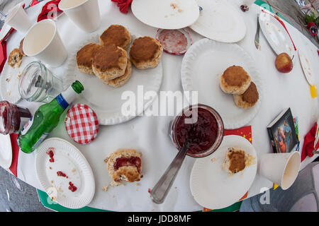 A messy tea party with scones and jam - Stock Photo
