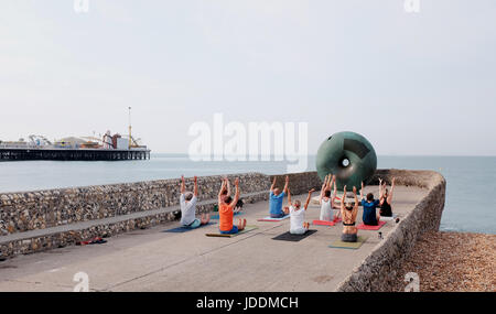 Brighton, UK. 20th June, 2017. A yoga class enjoys the continuing hot weather on Brighton seafront early this morning - Stock Photo