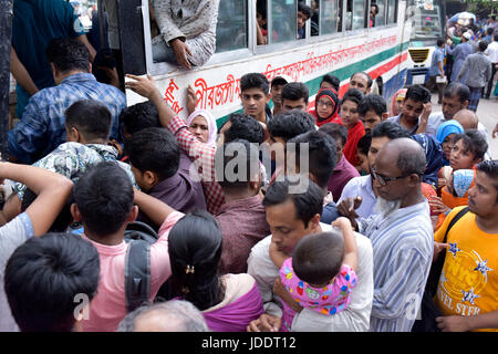 DHAKA, BANGLADESH - JUNE 20, 2017: Bangladeshi people try to ride in an overcrowded bus to travel home, as others - Stock Photo