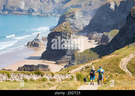 A man and woman couple walking down the path towards the beach at the popular attraction of Bedruthan Steps in Cornwall - Stock Photo