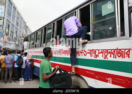 Dhaka, Bangladesh. 20th June, 2017. Bangladeshi people try to ride in of an overcrowded bus to travel home, as others - Stock Photo