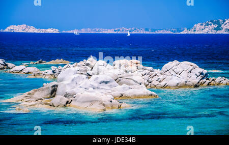 Granite rocks in sea, amazing azure water, white sailboats in background near Porto Pollo, Sardinia, Italy. - Stock Photo