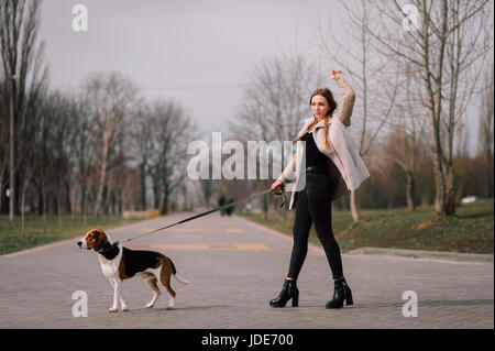 Young hipster girl with her pet estonian hound dog playing and having fun outdoor in the park. - Stock Photo