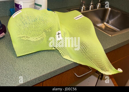 Patient Radiation therapy mask showing laser markings for targeting cancer cells in the brain being repaired - Stock Photo