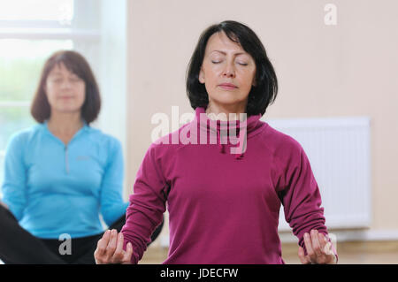 Two mature women sit on the lotus position. Focus on the first lady. Healthy fitness concept with active lifestyle. - Stock Photo
