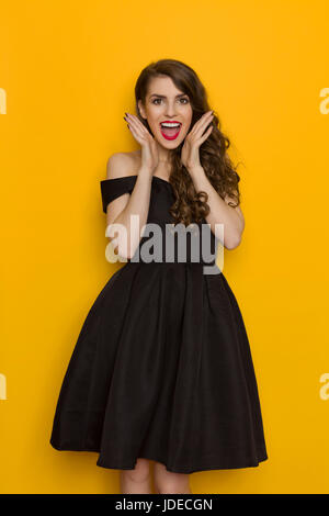Amused beautiful young woman in elegant black cocktail dress is shouting and looking at camera. Three quarter length - Stock Photo
