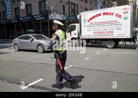 New York City cop directing traffic at busy intersection USA - Stock Photo