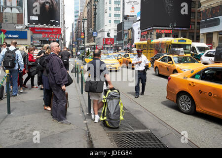 people waiting at yellow cabs stop at taxi rank on 7th avenue outside penn station New York City USA - Stock Photo