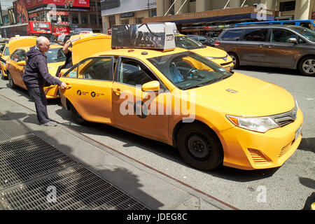 man getting in to yellow cab stop at taxi rank on 7th avenue New York City USA - Stock Photo