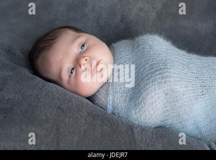 Newborn baby wrapped in knitted warm blanket. Beautiful portrait of a newborn baby who is awake and looks around. - Stock Photo