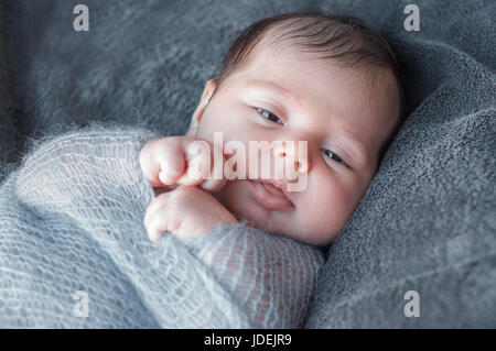 Newborn baby wrapped in knitted warm blanket. Beautiful closeup portrait of a newborn baby who is awake and looks - Stock Photo