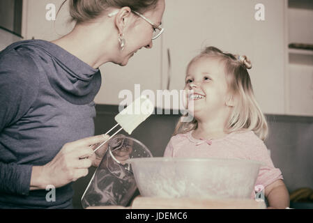 Mother and little toddler daughter having fun whilst baking in the kitchen. Instagram effect. - Stock Photo