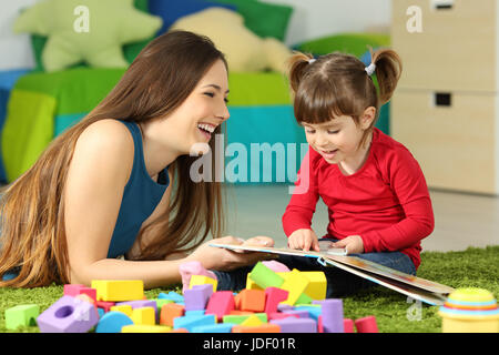 Mother and toddler playing together with a book lying on the floor in the bedroom at home with a colorful background - Stock Photo