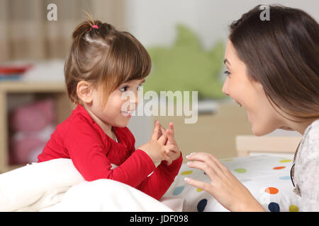 Mother and toddler wearing red shirt playing together on a bed in the bedroom at home - Stock Photo