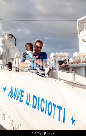 Palermo, Italy. 19th June, 2017. Migrants disembark from an Italian Coast Guard ship at a dock in Palermo, Italy - Stock Photo
