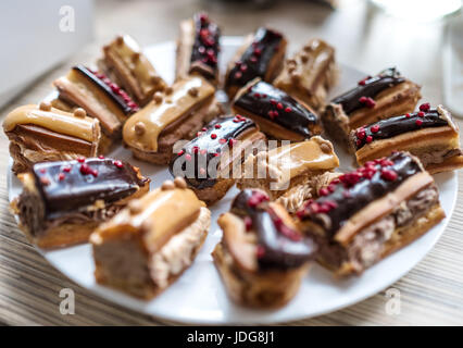 Cakes eclairs on a plate, selective focus - Stock Photo