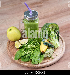 Fresh green vegetables, fruits and green smoothie in jar. Detox, diet or healthy food concept. Mason jar of dietary - Stock Photo