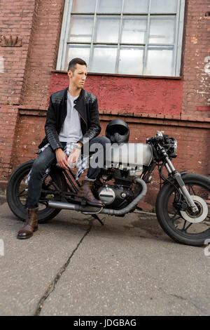 Handsome rider biker man in black leather jacket, jeans and boots sit on classic style cafe racer motorbike. Bike - Stock Photo