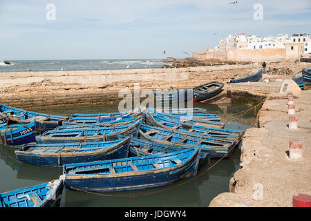 Blue painted boats belonging to fisherman lie inside the old harbour of Essaouira, Morocco - Stock Photo