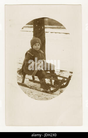 Early 1900's postcard of boy on sledge, possibly German, circa 1930's - Stock Photo