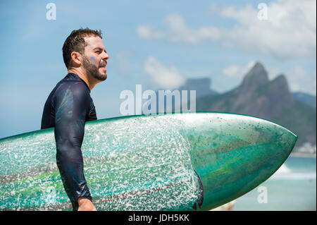 RIO DE JANEIRO - FEBRUARY 10, 2017: Brazilian surfer walks with surfboard along the shore at Arpoador with two brothers - Stock Photo