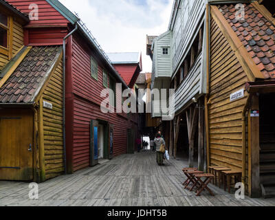 Tourists in Jacobsfjorden and Bellgarden with Hanseatic commercial wooden buildings on each side of passageway Bryggen - Stock Photo