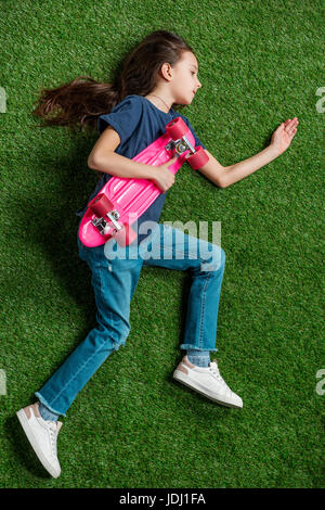 Top view of cute little girl with pink skateboard lying on green lawn - Stock Photo