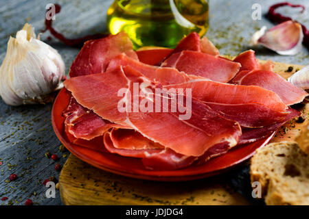 closeup of an earthenware with some slices of spanish serrano ham on a wooden chopping board, and some slices of - Stock Photo