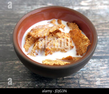 Wheat bran breakfast cereal with milk in clay bowl on wooden background - Stock Photo