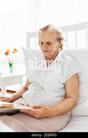Elderly woman sitting comfortably in bed reading her favourite book at home - Stock Photo