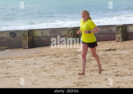Young woman running bare footed along seashore at Bournemouth beach at Bournemouth, Dorset in April - Stock Photo