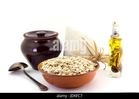 Still life of Porridge oate in ceramic pial, ceramic pot, old spoon and canvas bag for cereals, oil with spices - Stock Photo
